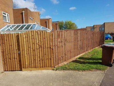 6 foot tall feathered edge fence with a curved over top and a gate