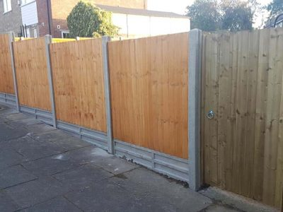 brown wood feathered edge fence with concrete gravel boards