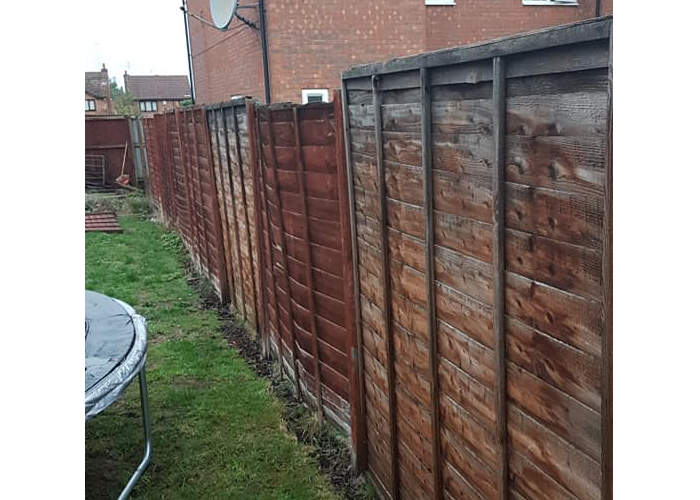 before of a fence installation of a new six foot tall fence surrounding the a large garden