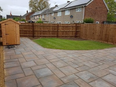 full garden installation of a brown wood six foot tall fence with timber gravel boards