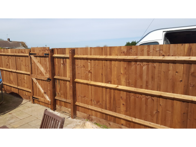 yellow fencing boards wiht a gate installed in the middle