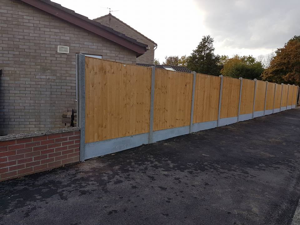 garden fence installed against drive way in corby